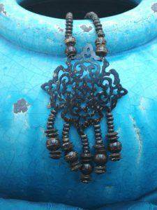 Pendant in carved coconut, natural jewelry on blue ceramic.