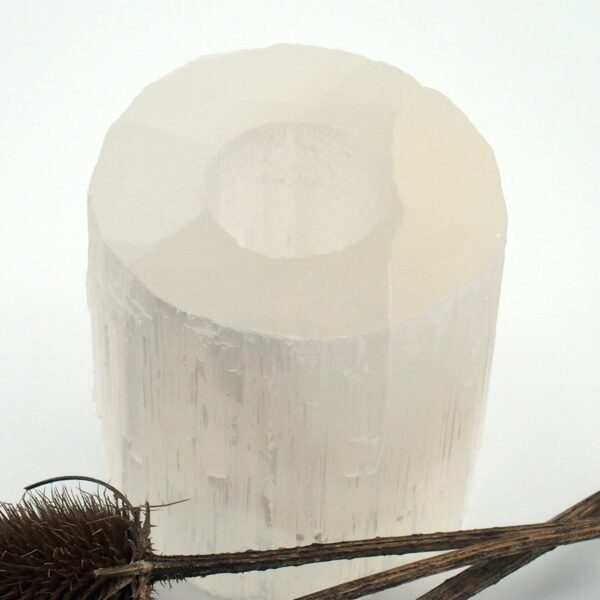 Selenite tealight holder on a white background with thistle seed heads in front, showing the transparent nature of this stone.