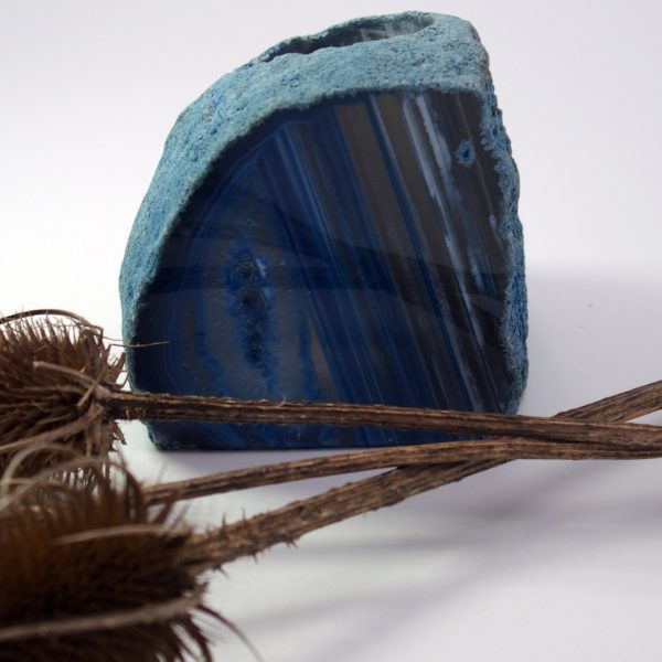 Blue agate tealight holder natural cut on white background with thistle seedpods.